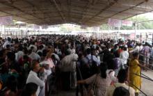 People standing in queue for fish medicine