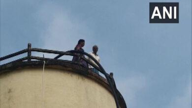 Photo of AP: Elderly couple climbs water tank demanding land money