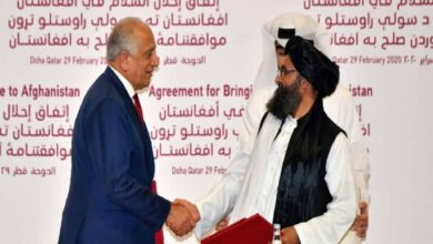 US negotiator Zalmay Khalilzad shakes hands with Taliban co-founder Mullah Baradar after signing the landmark deal