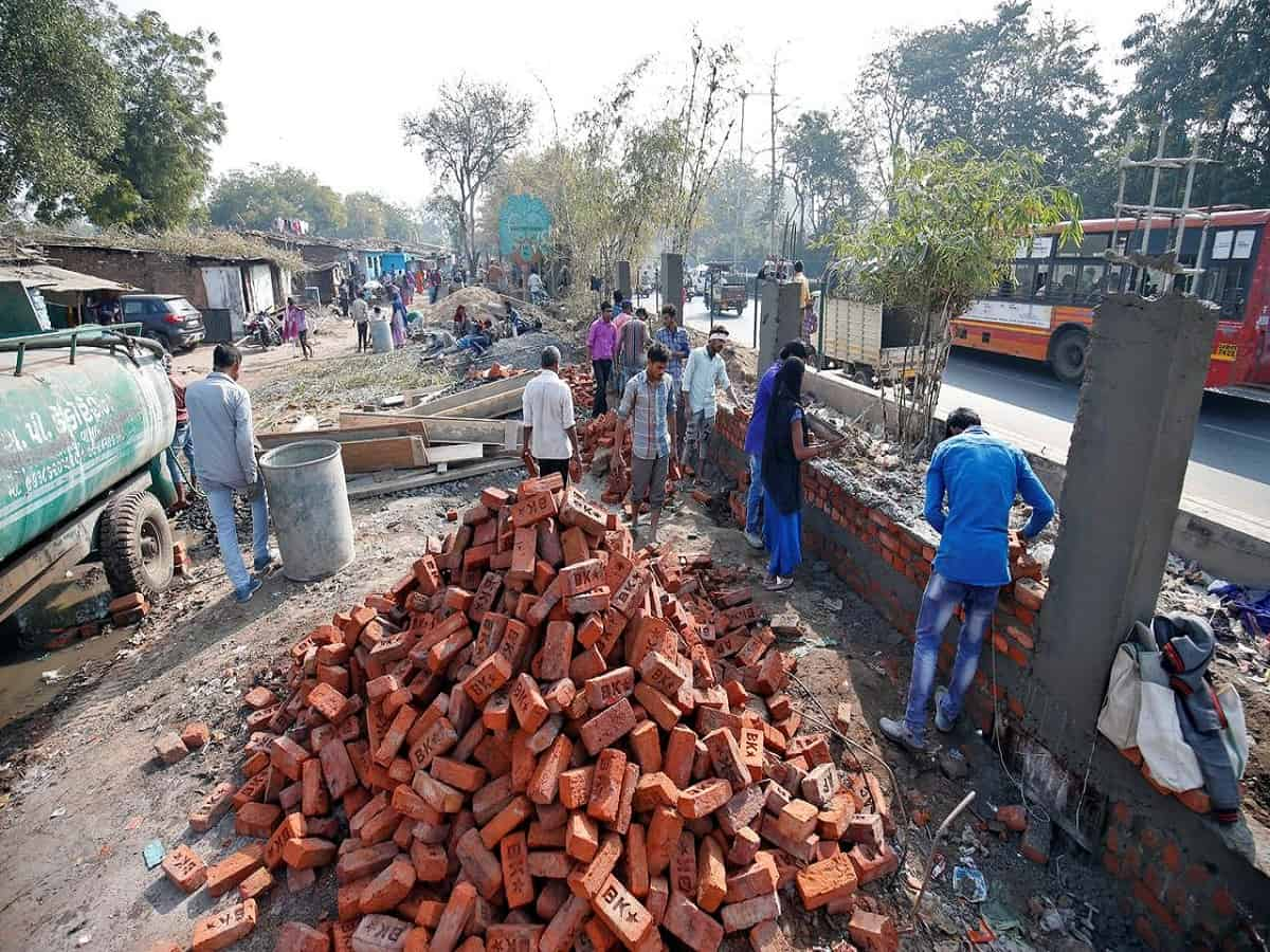 Wall being constructed to cover slum area in Gujarat