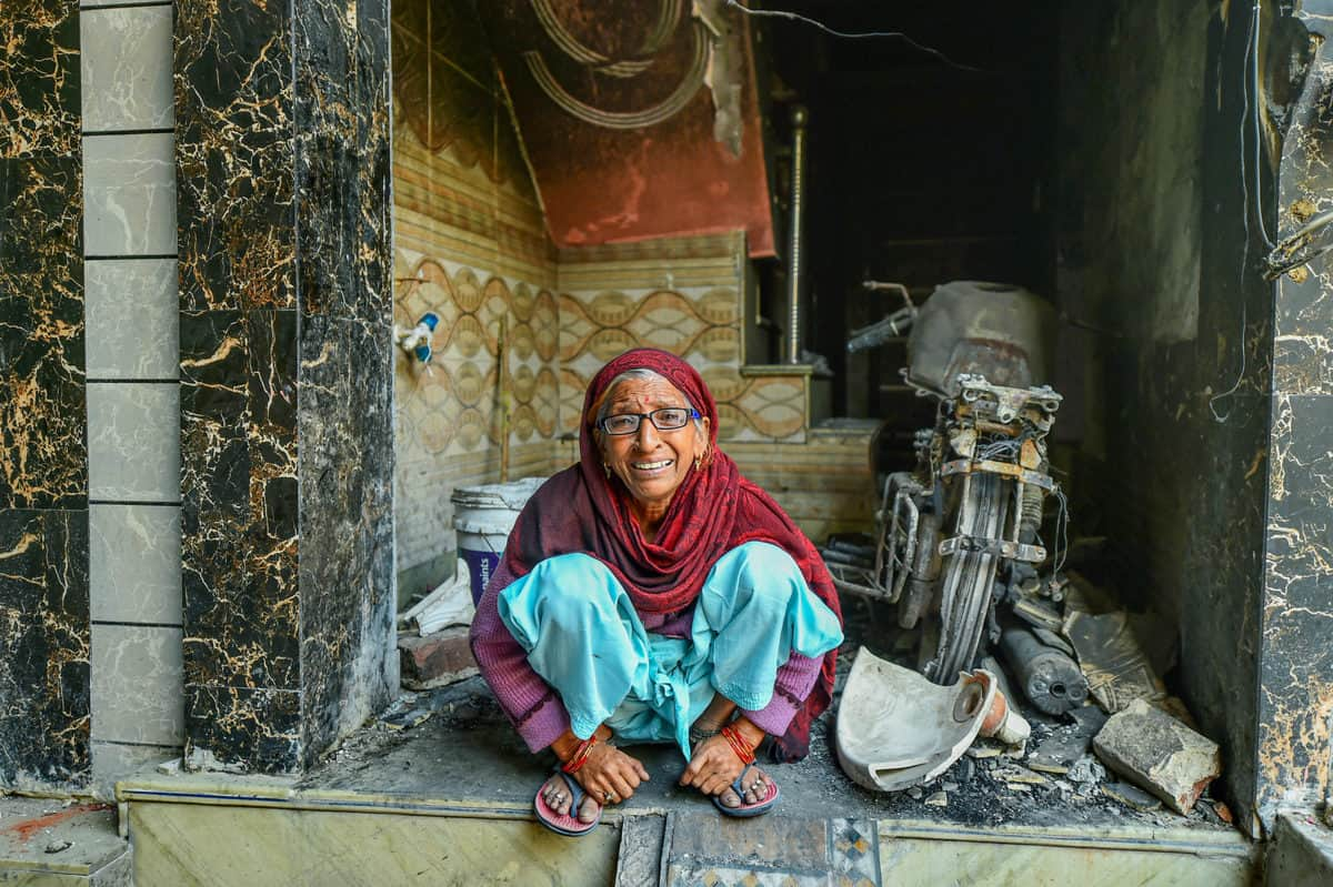 New Delhi: Munni Devi, a victim of recent communal violence, sits amid the charred remains of her house at Shiv Vihar in riot-affected Northeast Delhi, Monday, March 2, 2020. (PTI Photo)
