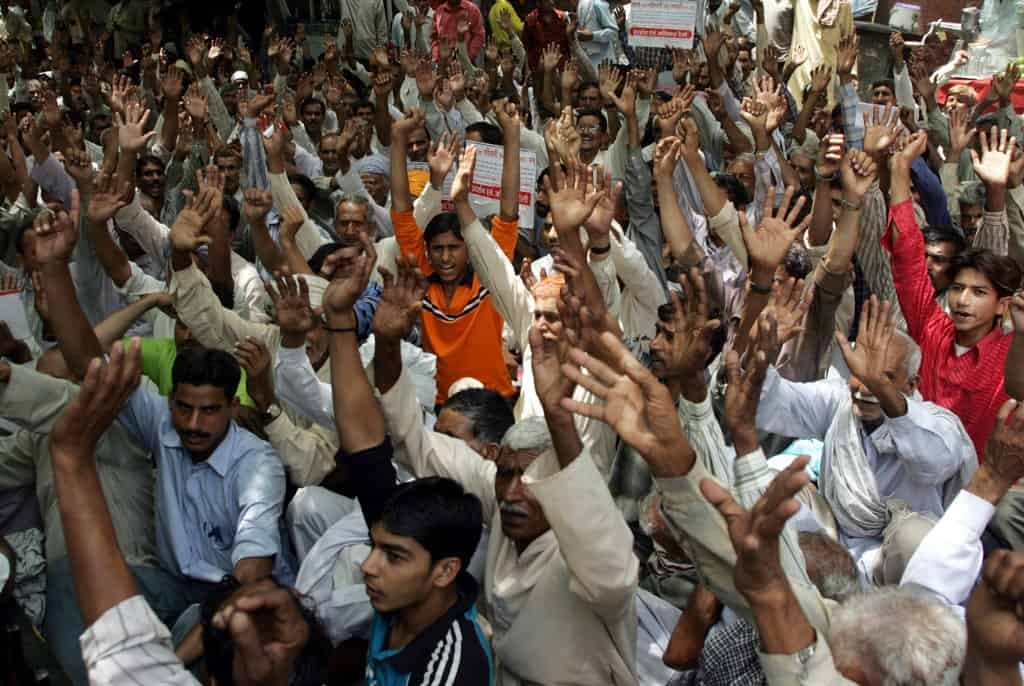 West Pakistani Hindu refugees shout slogans as they take part in a Human Rights demonstration near Parliament House in New Delhi, 18 May 2006. Hundreds of protesters demanded that the Indian government provide them with housing, land, government jobs and free education. AFP PHOTO/RAVEENDRAN (Photo by RAVEENDRAN / AFP)