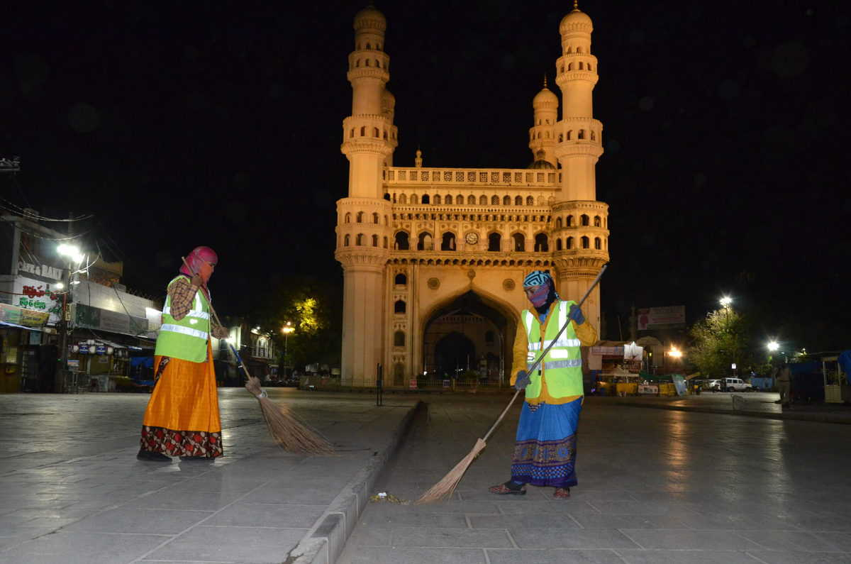 GHMC sanitation staff cleaning the deserted footpath near Charminar during lockdown in Hyderabad. Photo: Mohammed Hussain