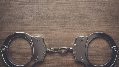 steel handcuffs on the wooden background