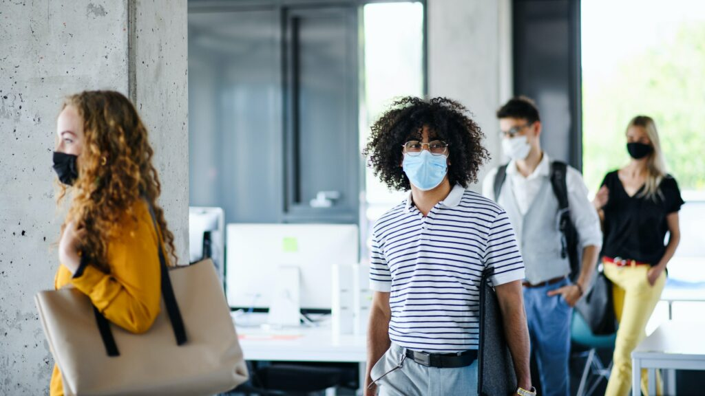 Young people with face masks back at work in office after lockdown, walking