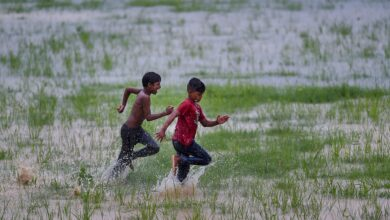 Photo of Children run in a waterlogged field after heavy rains in Ghaziabad