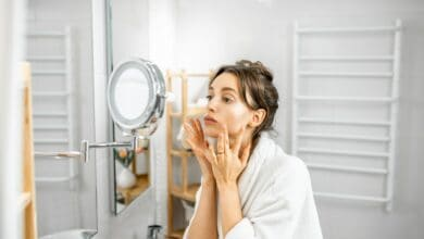 Woman looking on her skin at bathroom