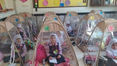 Photo of Iran: Students sit inside a plastic tent to maintain social distancing