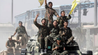 Kurdish militia ride atop military vehicles as they celebrate victory over Daesh in Raqqa, Syria